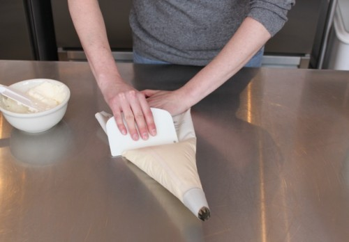 Use your bowel scraper to push all the icing down toward the tip.